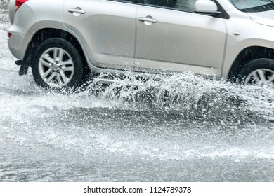 car traffic during rainy day. splashes of water from car wheels