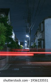 A car traffic Light trails Streak making red light rays in the dark by night feeling the energy of the urban scenery surrounded by power lines in Tokyo.