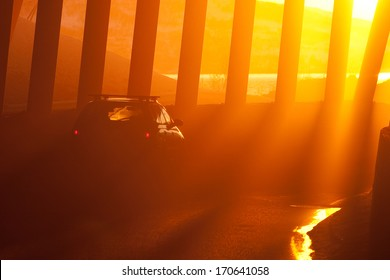 Car in trafic dust against low sun