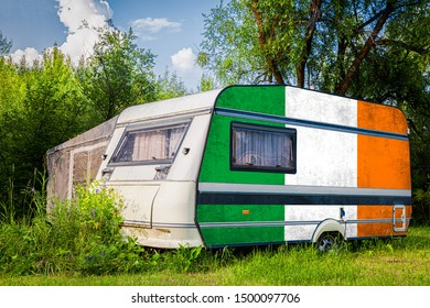 A car trailer, a motor home, painted in the national flag of  Ireland stands parked in a mountainous. The concept of road transport, trade, export and import between countries.