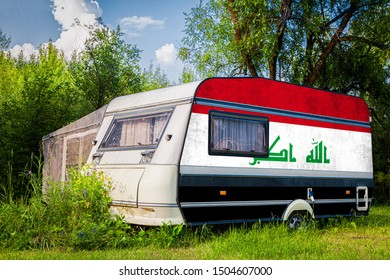 A car trailer, a motor home, painted in the national flag of  Irak stands parked in a mountainous. The concept of road transport, trade, export and import between countries.