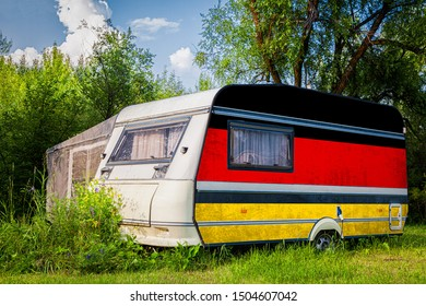 A car trailer, a motor home, painted in the national flag of  Germany stands parked in a mountainous. The concept of road transport, trade, export and import between countries.