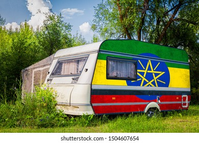 A car trailer, a motor home, painted in the national flag of  Ethiopia stands parked in a mountainous. The concept of road transport, trade, export and import between countries.