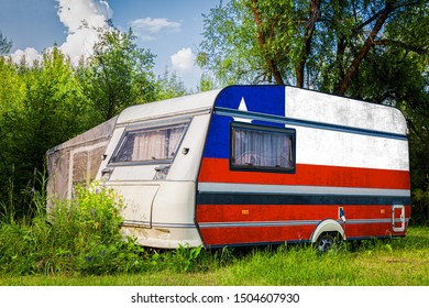 A car trailer, a motor home, painted in the national flag of  Chile stands parked in a mountainous. The concept of road transport, trade, export and import between countries.