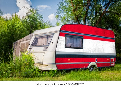 A car trailer, a motor home, painted in the national flag of  Austria stands parked in a mountainous. The concept of road transport, trade, export and import between countries.