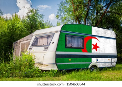 A car trailer, a motor home, painted in the national flag of  Algeria stands parked in a mountainous. The concept of road transport, trade, export and import between countries.
