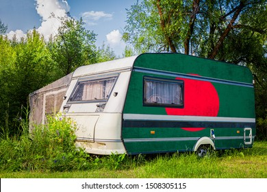 A car trailer, a motor home, painted in the national flag of  Bangladesh stands parked in a mountainous. The concept of road transport, trade, export and import between countries.