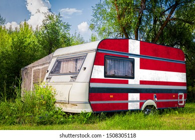 A car trailer, a motor home, painted in the national flag of  Denmark stands parked in a mountainous. The concept of road transport, trade, export and import between countries.