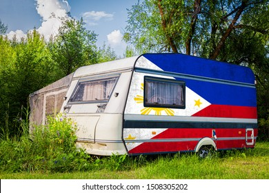 A car trailer, a motor home, painted in the national flag of  Philippines stands parked in a mountainous. The concept of road transport, trade, export and import between countries.