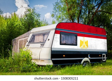 A car trailer, a motor home, painted in the national flag of  Egypt stands parked in a mountainous. The concept of road transport, trade, export and import between countries.
