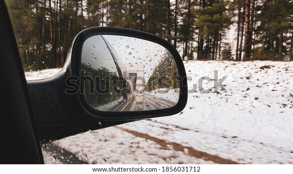 Car with trailer travel trip active vacation on cloud winter day, indoor view from car to front side window to outdoor back view mirror caravan trailer reflection. Winter journey  concept