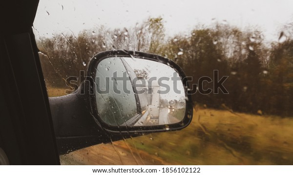 Car with trailer travel trip active vacation in rainy day, indoor view from car to front side window to outdoor back view mirror caravan trailer reflection. Journey and caravan travel concept