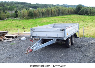 car trailer. car trailer with two wheel axle, Loaded silver car trailer at the Storage Place in a countryside Froland. Norway. Easy to move thing around the country and comfortable transportation.