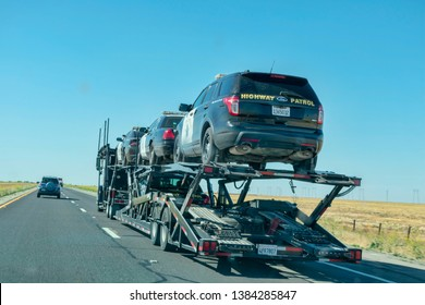 Car transporter carries California highway patrol cruisers along the highway, back view of the trailer - Lost Hills, California, USA - April 22, 2019