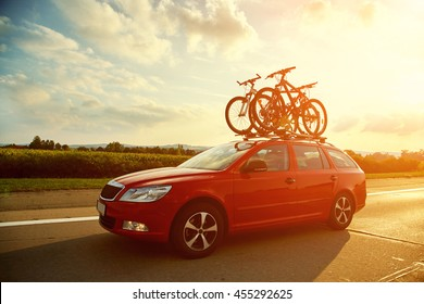 car is transporting bicycles on the roof. bikes on the trunk
