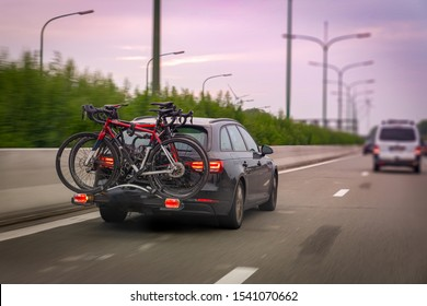 Car transports bicycles on a rack on highway in early morning