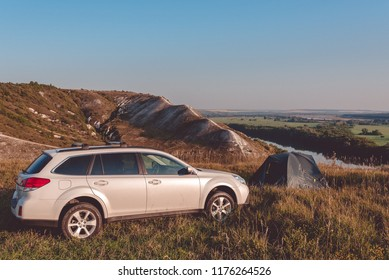 Car travel. Car camping. Car trip. Road trip. Travel concept: SUV and camping tent on top of the mountain