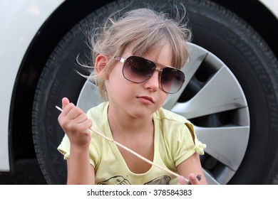 Car travel with a child. Picture of a little girl seating on a roadside against the car wheel