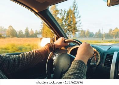 car travel concept man hand on steering wheel speedway