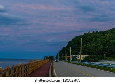 Car traveling on two lane country road along oceanside boardwalk under blue sky with white and pink clouds at sunset.