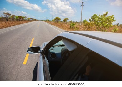 A car travels on a straight road, with the local vegetation abroad, in Amapa, Brazil