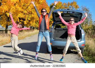 Car trip on autumn family vacation, happy mother and kids travel and have fun, car insurance concept