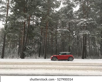 The car trip in the snow forest. Mini Cooper on road made a stop