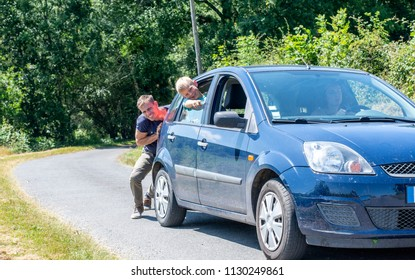 Car trouble. Man pushing car with family on hot day. No fuel.