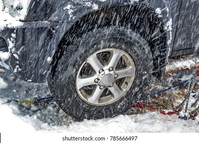 Car tyre and chains during snow storm.