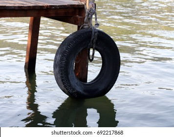 a car tyre hanging on the deck to the sea