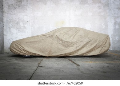 Car under a protective cover parked in parking garage