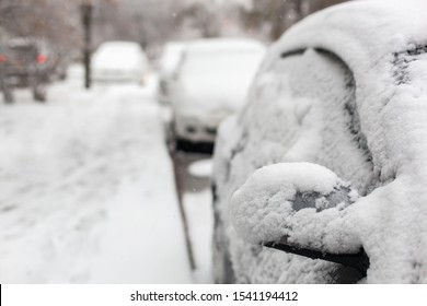 Car under the snow on the city street in winter day after cyclone or blizzard. Cars after snowfall. Wet snow covered parked car.