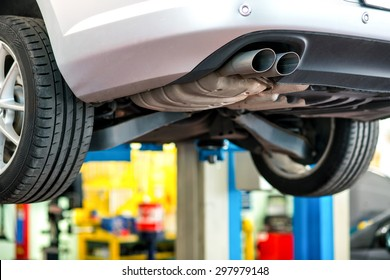 Car undergoing repair or a service in a workshop raised on a lift or hoist with focus to the exhaust pipe