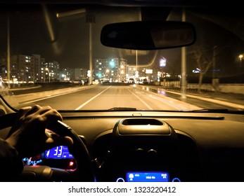 car use on night road. man holding steering wheel in car