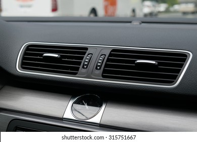 Car ventilation vent with an analog watch inside of a car.