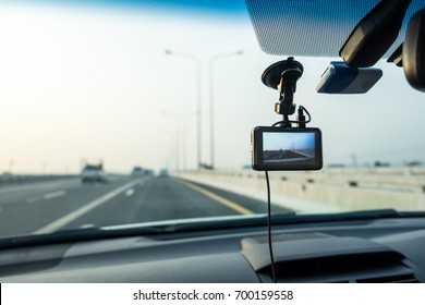 Car video camera (dash cam) installed inside of car with blurred background of highway road, looking from perspective of the driver. Concept of safety camera for car protection, technology for safety