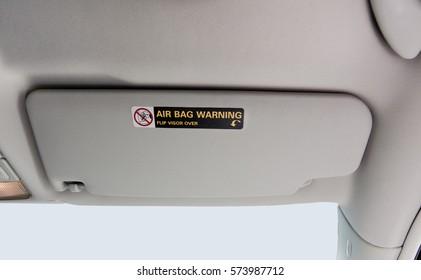 Car visor with air bag message.
