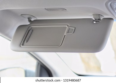 Car visor. Car interior. Grey open sun car visor with selective focus and car mirror on blurred background with automobile window