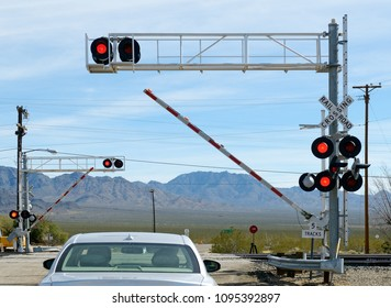 Car waiting at railroad crossing. Opening or closing barrier in the middle of movement.