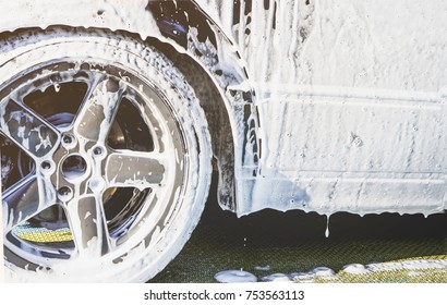 Car wash Closeup tires rims disk wheel and tire . Modern car wash with high pressure water. Delicate touchless car wash with soap suds. A lot of foam after washing.