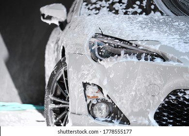 Car wash concept. Front view of white sports car covered with water, washing foam, and soap on hood & bumper. Professional car detailing & commercial cleaning service concept. Wet car background. - Shutterstock ID 1778555177