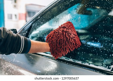 Car wash and detailing - the man holds the microfiber in hand and polishes or washing the car. Man cleaning automobile with sponge at car wash