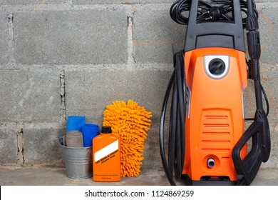 Car wash equipment or car cleaning product such as microfiber tank and pressure washer and glass cleaner and brush with mitts and etc, on cement floor.