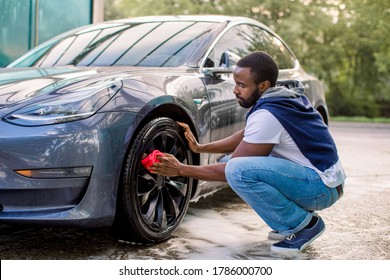 Car wash service outdoors. Car wash self-service concept. Handsome African guy wiping wheel of his modern luxury electric car with red cloth during the washing process outdoors