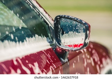 Car wash with soap. Manual car wash with pressurized water in car wash outside.Summe Washing. Cleaning Car Using High Pressure Water. Washing  with soap. Close up concept.