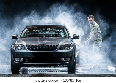 A car washer washes a gray car with a high-pressure washer at night on the street. Expensive advertising photography