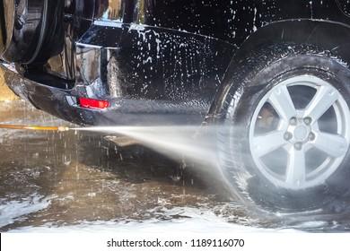Car washing. Cleaning car with high pressure water and foam.