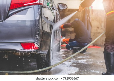 Car washing. cleaning car  worker using high pressure water.