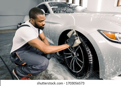Car washing and detailing photo. African man worker in protective overalls and rubber gloves, washing car wheel rims of luxury white, on a car wash, using sponge and foam cleaning solution