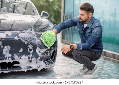 Car washing outdoors ar self wash service station. Handsome bearded man in casual wear, washing his car headlights with green sponge and soap